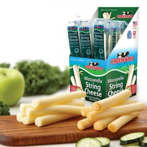 Carton of Opened 1 oz Cheesewich regular flavor cheese sticks. Nice cutting board with string cheese piles woth apple, cucumber very healthy and appetizing looking.