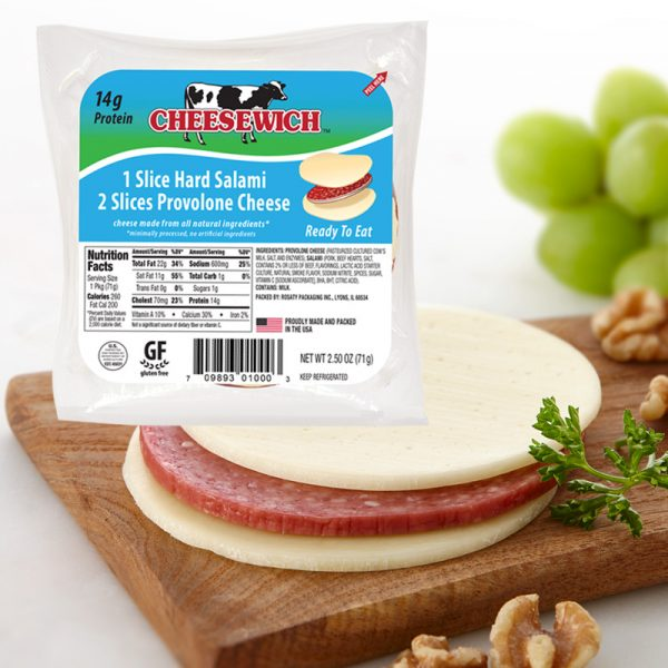 Provolone Cheesewich™ cheese and salami sandwich on a cutting board with walnuts and parsely and green grapes. 2 Slices of Provolone Cheese and 1 Slice of hard Salami.